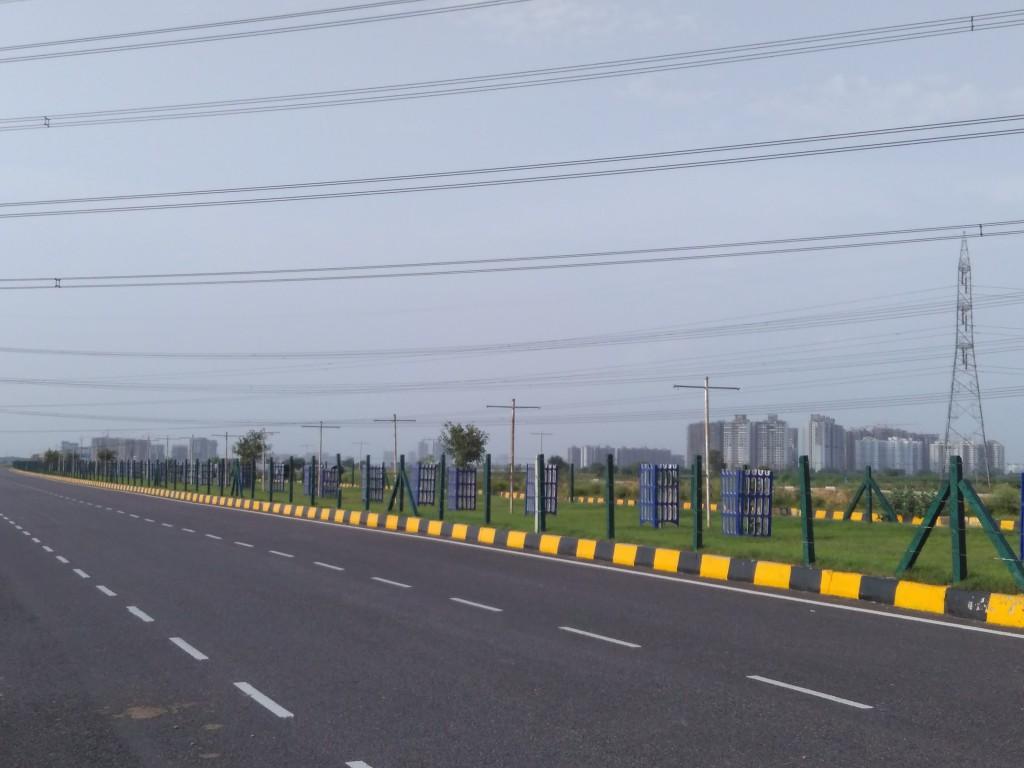 Driving on Dwarka Expressway in between Vatika Express City and Ramprastha City