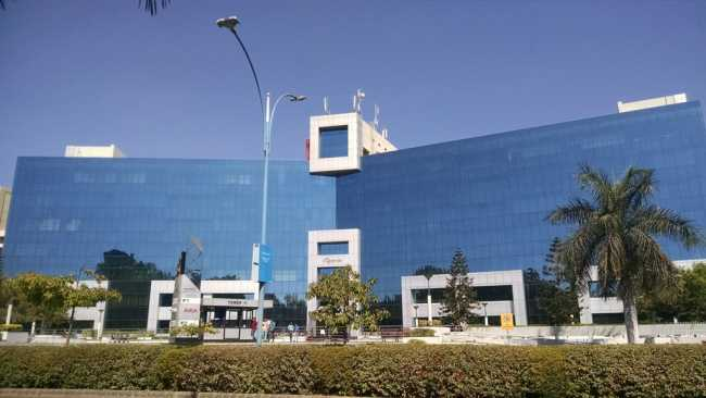 View of a glass-exterior office building at Cybercity IT Park in Magarpatta City