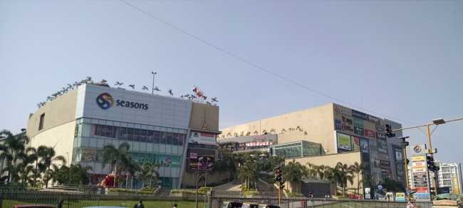 Front-view of Seasons Mall in Magarpatta City, lined with palm trees and lawns
